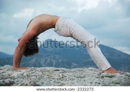 Man doing a bridge on rock - stock photo