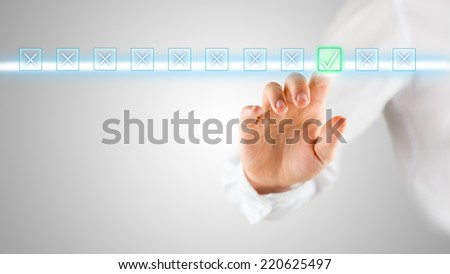 Man doing an evaluation or assessment online activating a check mark or tick on a highlighted bar with boxes on a virtual screen, with copyspace over grey. - stock photo