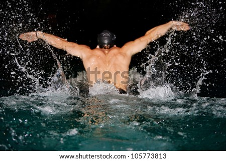 Man doing butterfly strokes while swimming in a pool at night. Dramatic water splashing. - stock photo