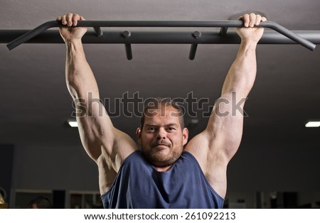 Man doing exercises at gym, training dorsal muscle - stock photo