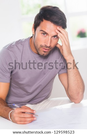Man doing his accounting and looking at camera in kitchen - stock photo
