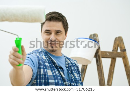 Man doing home improvement, painting with roller. Isolated on white background. - stock photo