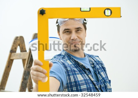 Man doing home improvement, using square level tool. Isolated on white background. - stock photo