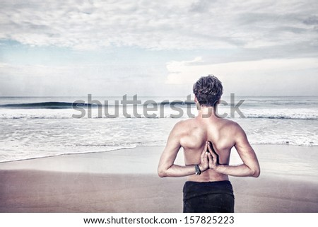 Man doing Namaste behind his back and looking to the ocean - stock photo