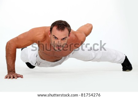 Man doing one-armed push-up - stock photo
