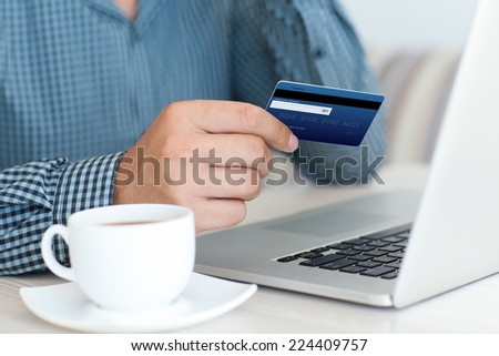 man doing online shopping with credit card on laptop - stock photo