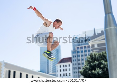 Man doing parkour in the city on a sunny day - stock photo