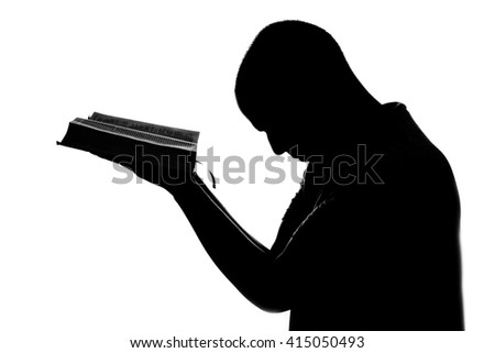 Man doing prayer with the holy bible in his hands. Back light black and white. - stock photo