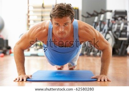 Man Doing Press Ups In Gym - stock photo