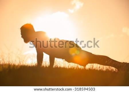 Man doing push ups outdoors - stock photo