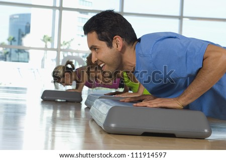 Man doing pushups on a step in aerobics class - stock photo