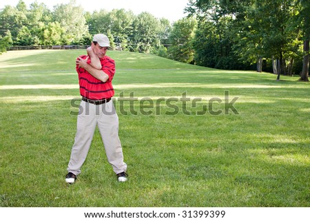 Man doing several stretching exercises before round of golf. - stock photo