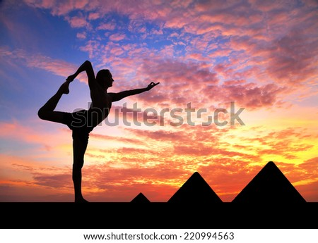 Man doing yoga at Egyptian Pyramids background in silhouettes - stock photo
