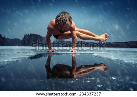 Man doing yoga exercise (parsva bakasana) on the ice of frozen lake at winter snowy day - stock photo