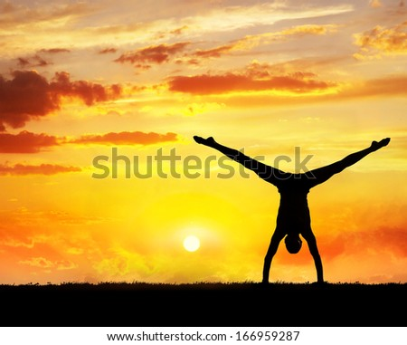 Man doing Yoga handstand on the grass at sunset sky - stock photo