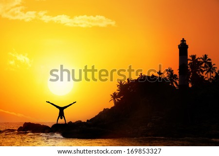 Man doing Yoga handstand on the rocks near lighthouse at sunset sky - stock photo