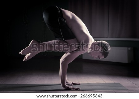 man doing yoga in a sports hall - stock photo