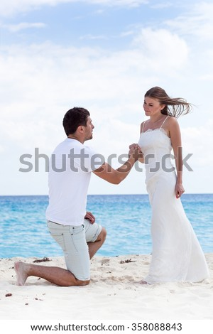 Man down on one knee and asking for marry his woman, holding her hand on sandy beach near sea at Caribbean vacation. Free copyspace on sky background.  - stock photo