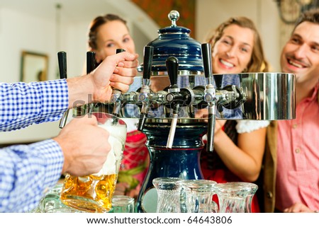 Man drawing a beer from tap on a kegerator in pub or inn, people in Bavarian Tracht are standing in the background - stock photo