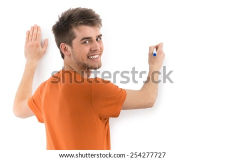 man drawing on white wall and smiling. back view of man looking at camera and holdig marker - stock photo