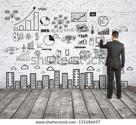 man drawing strategy on brick wall - stock photo