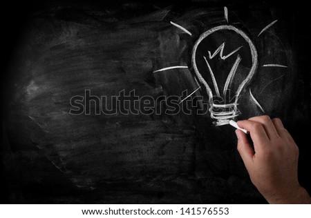 man draws a chalk lightbulb on a black school board - stock photo