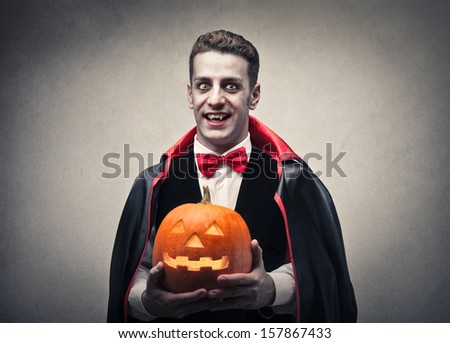 man dressed as Dracula with halloween pumpkin in hand - stock photo