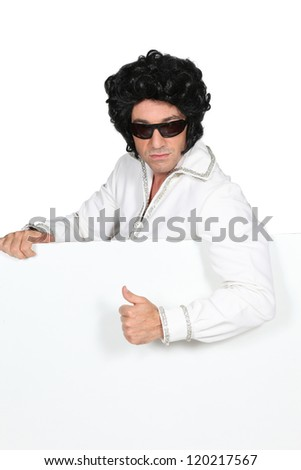 Man dressed as Elvis holding blank message board - stock photo