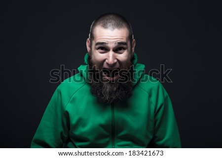 Man, dressed in a green swatshirt, screaming - stock photo