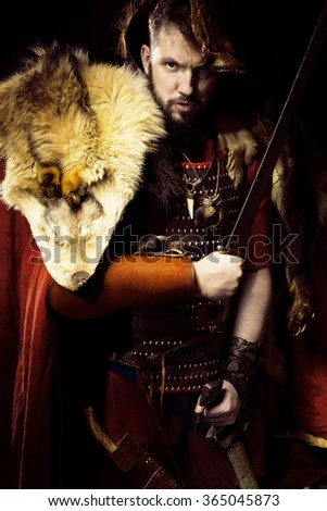Man dressed in barbarian style with sword and moustache, bearded over black background and angry look - stock photo