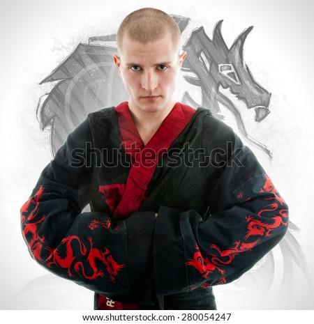 Man dressed in black dragon kimono demonstrating martial arts combat - stock photo