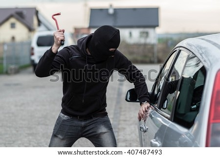 Man dressed in black with a balaclava on his head breaking a glass in car with crowbar. Car thief, car theft concept - stock photo