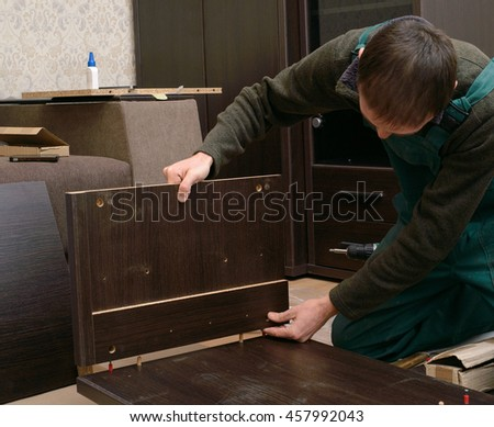 Man dressed in workers' overall assembling furniture sitting on the floor in new home. DIY, home and moving concept - stock photo