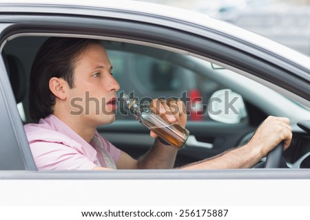 Man drinking alcohol while driving in his car - stock photo