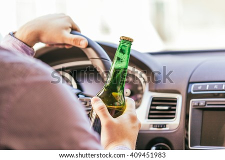 man drinking alcohol while driving the car - stock photo