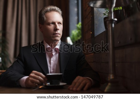 Man drinking coffee at the restaurant Thoughtful mature businessman drinking coffee at the restaurant - stock photo