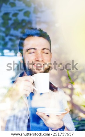 man drinking coffee in the morning (view through the window) - stock photo
