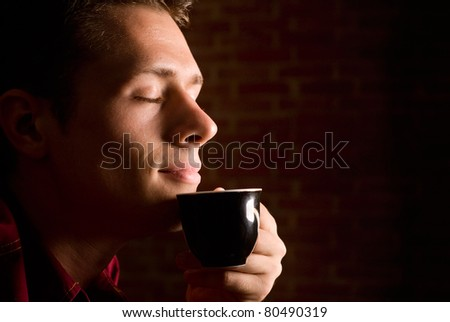 man drinking coffee on  a brick background - stock photo