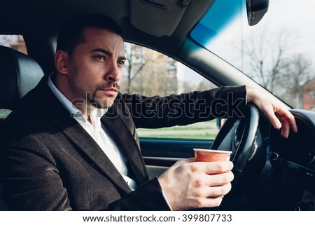 Man drinking coffee while driving the car - stock photo