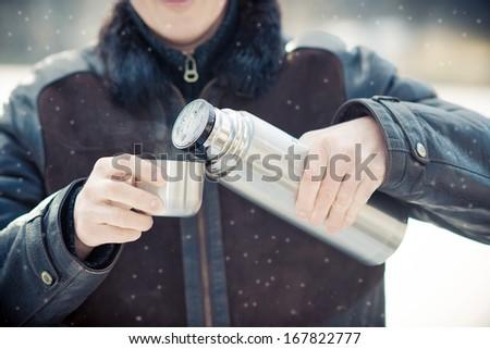 Man drinking hot tea outdoors - stock photo