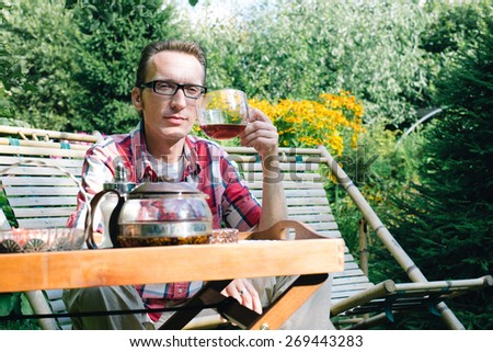 Man drinking tea in his own garden at summer day - stock photo
