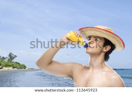 Man drinking water from a water bottle on the beach - stock photo