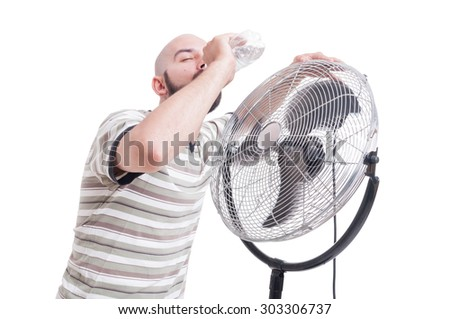 Man drinking water near blowing fan as summer heat dehydration concept - stock photo