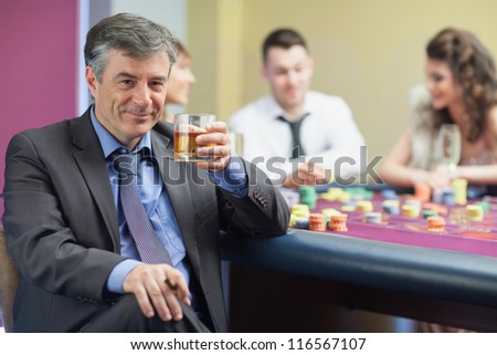 Man drinking whiskey at roulette table in casino - stock photo