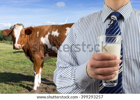 man drinks milk in front of a watching cow - stock photo