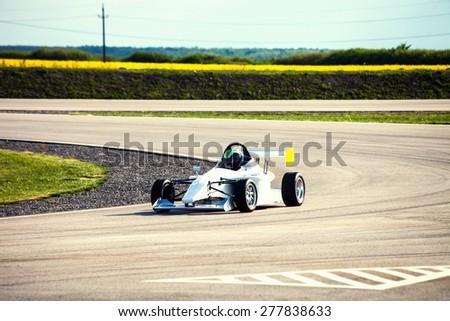 man drive race car on a track - stock photo