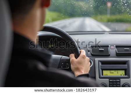 Man driving a car with his hands on the steering wheel - stock photo