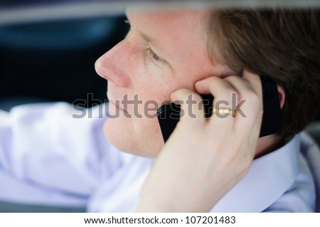 Man driving and talking on cell phone - stock photo
