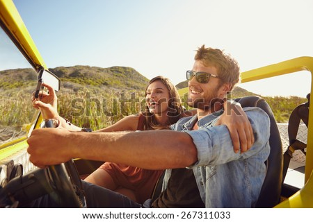 Man driving beach buggy with woman taking selfie on her smart phone. Couple having fun on road trip on a summer day. - stock photo