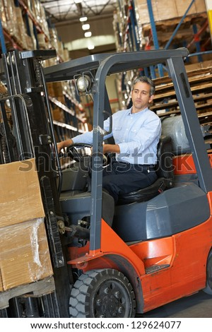 Man Driving Fork Lift Truck In Warehouse - stock photo
